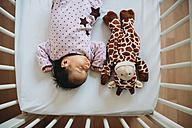 Newborn baby girl sleeping in crib with a plush giraffe - GEMF01377
