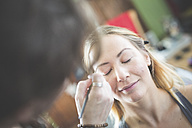 Stylist applying make up on woman's eyebrow - ASCF00678