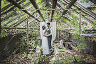 Bride and groom embracing in old greenhouse - ASCF00681
