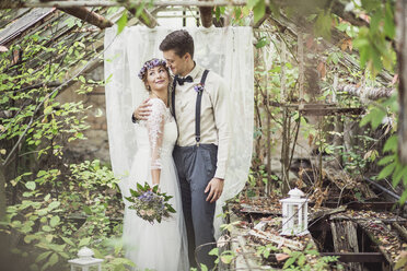 Bride and groom embracing in greenhouse - ASCF00690