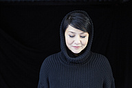 Smiling woman wearing hooded pullover - FMKF03452