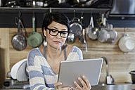 Woman in kitchen looking on tablet - FMKF03455