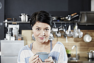 Portrait of woman in kitchen with cup of coffee - FMKF03458