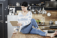 Woman sitting on table in kitchen looking on tablet - FMKF03461