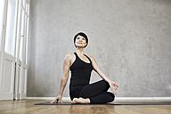 Woman practising yoga - FMKF03467