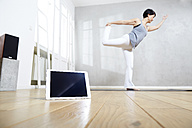 Woman practising yoga behind tablet - FMKF03470