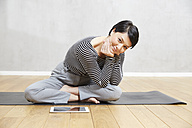 Smiling woman sitting on yoga mat with tablet - FMKF03473