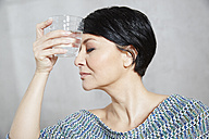 Woman holding glass of water to her forehead - FMKF03476