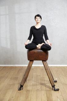 Woman practising yoga on pommel horse - FMKF03479