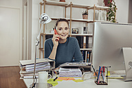 Woman talking on the phone in home office - MFF03424