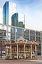 France, Paris, La Defense, old children's carousel in front of modern architecture - KLR00494