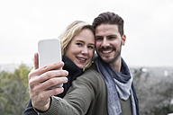 Smiling couple taking a selfie outdoors - ABZF01775