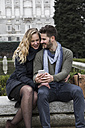 Spain, Madrid, happy couple with cell phone with the Royal Palace in background - ABZF01787