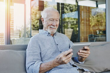 Senior man sitting on terrace reading ebook - RORF00438