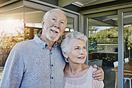 Senior couple standing in front of their house, looking confident - RORF00444