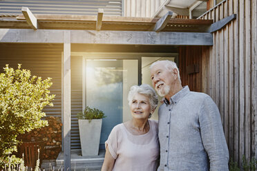 Senior couple standing in front of their house, looking confident - RORF00447