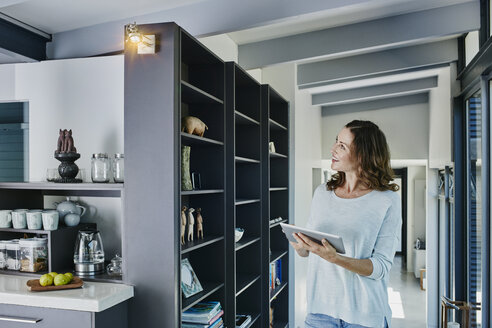 Woman regulating lamp with digital tablet - RORF00453