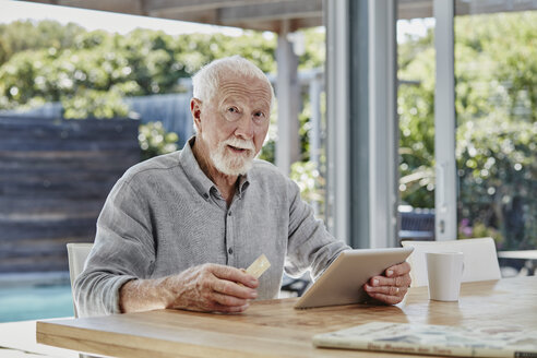 Senior man sitting on terrace, doing online payment with credit card - RORF00462