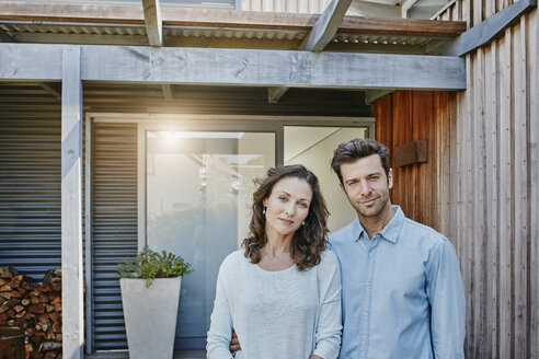 Couple standing in front of door of their home - RORF00468