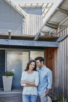 Couple standing in front of door of their home - RORF00471