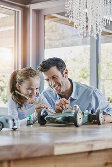 Father and daughter painting a toy race car - RORF00480