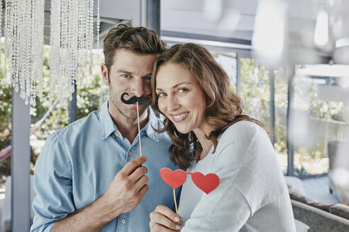 Couple with paper moustache and heart-shaped eye disguise - RORF00483