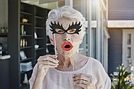 Senior woman hiding behind paper masks - RORF00492