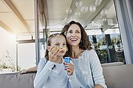Mother and daughter blowing soap bubbles on terrace - RORF00507