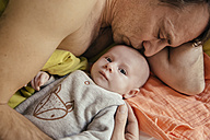 Father cuddling in bed with his newborn baby - MFF03456
