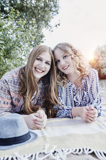 Portrait of two teenage girls relaxing on blanket on the beach - RORF00523