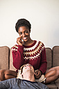 Portrait of young woman relaxing with her boyfriend in the living room - SIPF01319