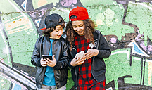 Two children standing in front of graffiti wall looking at cell phone - MGOF02789
