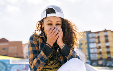 Portrait of laughing girl covering mouth with her hands - MGOF02807