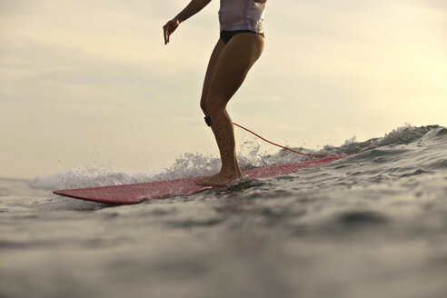 Indonesia, Bali, legs of woman on surfboard - KNTF00607