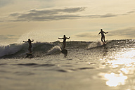 Indonesia, Bali, three surfers at sunset - KNTF00610