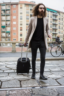 Stylish young man with suitcase crossing tramway - MAUF00928