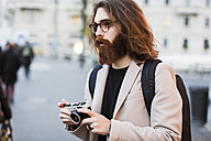 Stylish young man outdoors holding camera looking around - MAUF00943