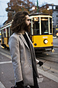 Stylish young man standing at tram stop - MAUF00952