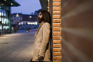 Stylish young man outdoors at night leaning against a brick wall - MAUF00967