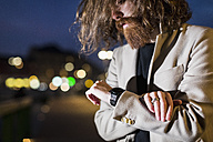 Stylish young man outdoors at night checking the time - MAUF00970