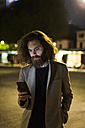Stylish young man outdoors in the city at night looking at cell phone - MAUF00973