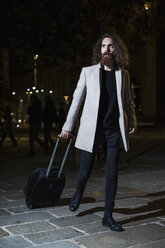 Stylish young man walking with suitcase at night - MAUF00976