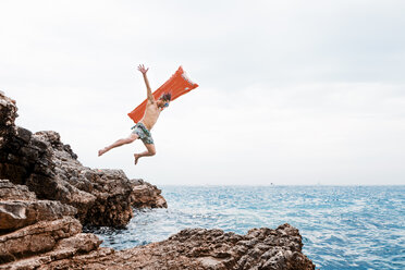 Man with airbed jumping from rock into the sea - WVF00774