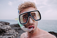 Portrait of young man with diving goggles and snorkel pulling funny faces - WVF00783