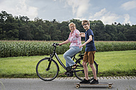 Grandson and grandmother riding bicycle and skateboard together - PAF01756