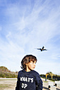 Little boy looking over shoulder to airplane in background - VABF01018