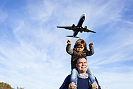 Father carrying son on shoulders under flying airplane - VABF01021