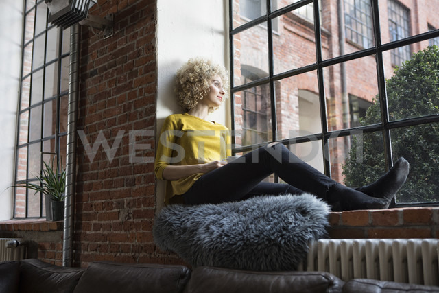 Young woman sitting on window sill, holding cup of coffee - RBF05529