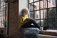 Young woman sitting on window sill - RBF05532