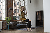 Young woman sitting on swing in living room - RBF05538
